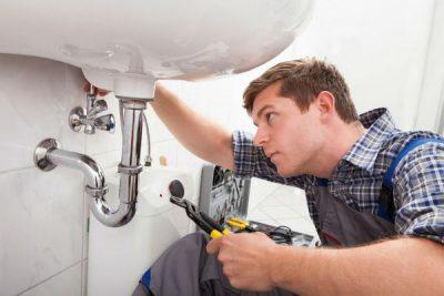 plombier répare un évier
