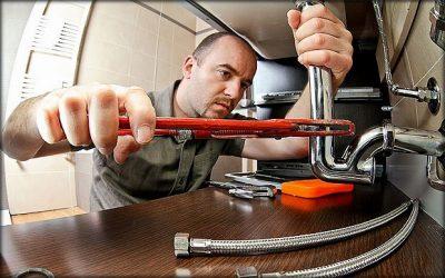 plombier sui resserre la tuyauterie de évier