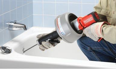 déboucheur qui débouche une baignoire avec un furet