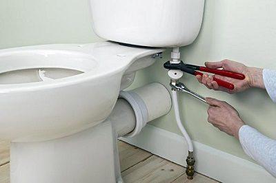 Plombier qui procède à une réparation fuite WC