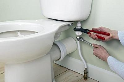 Plombier qui arrête une fuite WC