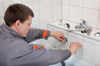 Plombier qui répare la tuyauterie lors d'un dépannage baignoire