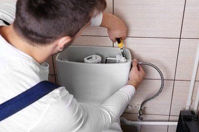 Plombier qui réalise une réparation fuite chasse d'eau