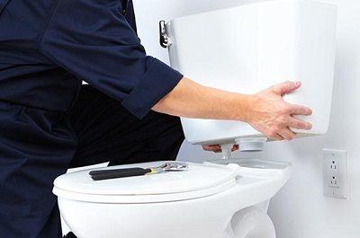 Plombier qui procède à un remplacement toilette pendant une réparation toilette