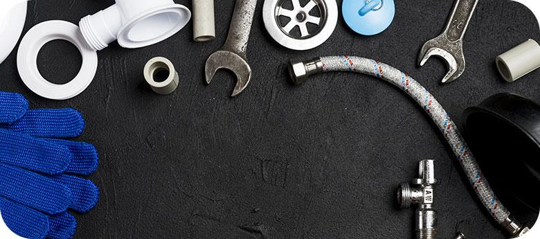 Ensemble de raccords de tuyauterie en PVC bleu isolé sur fond sombre. Bleu